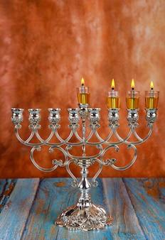 Зажигает свечи на третий день еврейского праздника ханука. горят свечи от меноры