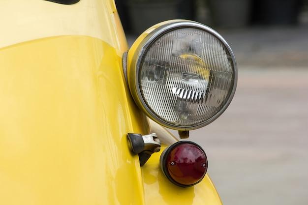 ユニークな球体を持つヴィンテージカーの前で点灯します。