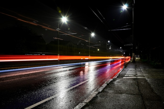 Огни машин в ночное время. уличные фонари. ночной город. фотография ночной дороги с длинной выдержкой. цветные полосы света на дороге. мокрая дорога после дождя.