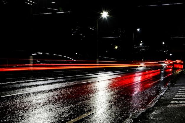 夜の車のライト。街灯。夜の街。長時間露光写真の夜道。道路上の色付きの光の帯。雨上がりの濡れた道路。