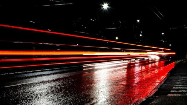 밤에 자동차의 조명입니다. 가로등. 밤 도시입니다. 장시간 노출 사진 야간 도로. 도로에 빛의 색된 밴드입니다. 비 온 후 젖은 길.