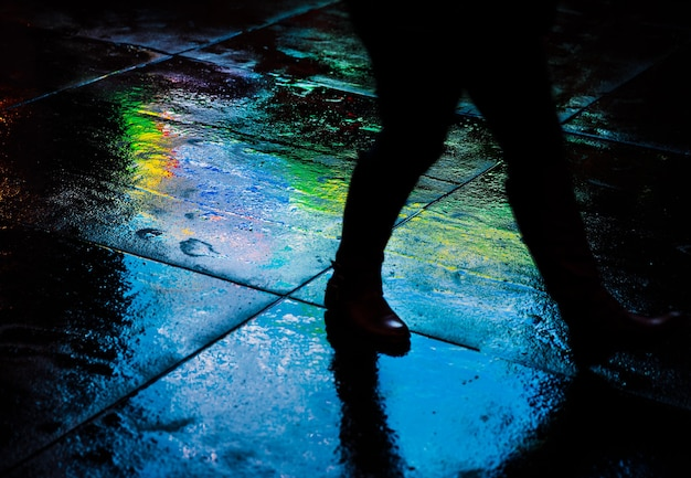 Lights and shadows of new york city. nyc streets after rain with reflections on wet asphalt. silhouettes of people walking on the street
