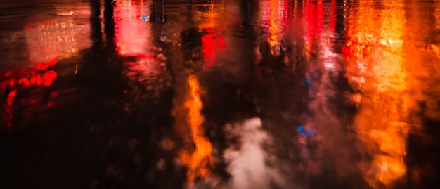 Lights and shadows of new york city. soft focus image of nyc streets after rain with reflections on wet asphalt