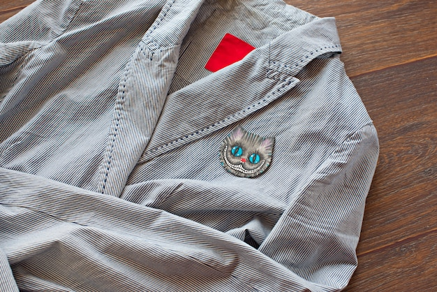 Lightweight striped cotton jacket with a fashionable brooch on wooden background