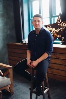 Портрет улыбающегося красавец, сидя на стуле в украшенной студии, глядя на камеру. уверенный брюнет мужчина в черном носить против ligth звезд на подоконнике.