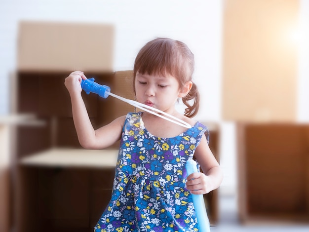 Liitle cute girl blowing soap bubbles in playroom.