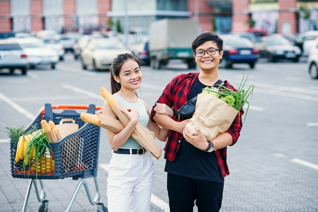 Likable asian couple hold paper eco bags with organic healthy food in hands while standing near store mall.