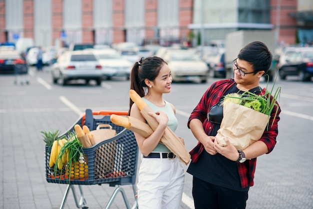 Likable asian woman and handsome vietnamese young man look to each other holding paper eco bags with organic healthy food in hands near store mall. family shopping on weekend.