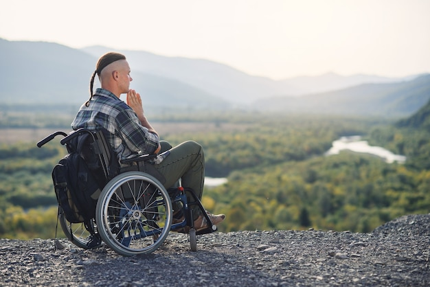 Likable incapacitated young guy sitting alone in wheelchair on the hill on beautiful nature