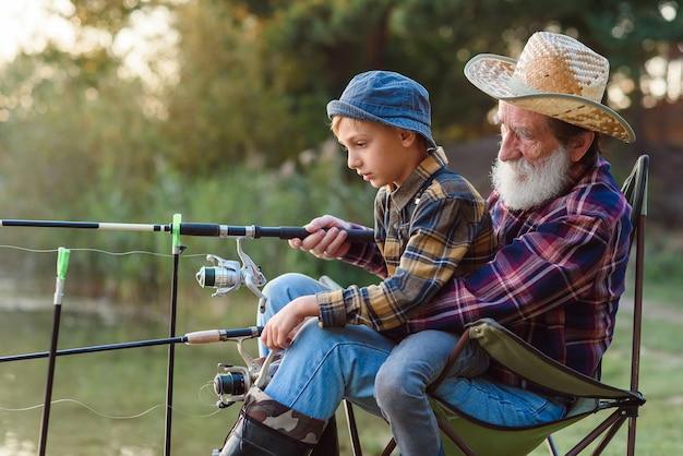 Симпатичный уважаемый 70-летний бородатый дедушка держит на коленях симпатичного 10-летнего внука и учит его ловить рыбу.