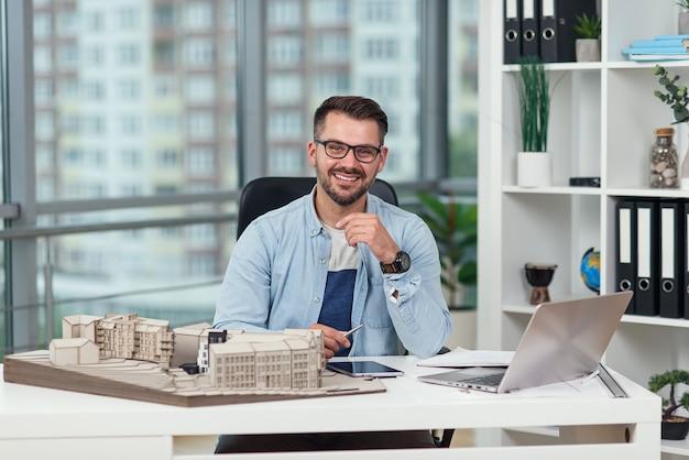 Симпатичный улыбающийся успешный бородатый 35-летний архитектор в очках сидит на своем рабочем месте с макетом
