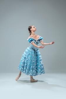 인형처럼. 회색 스튜디오 배경에 고립 된 아름 다운 현대 볼룸 댄서. 왈츠, 탱고, 슬로우 폭스, 퀵 스텝을 춤추는 감각적 인 프로페셔널 아티스트. 유연하고 무중력.