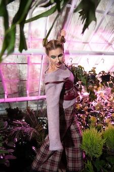 おとぎ話のように。ポーズをとりながら美しい植物の間に立つ魅力的な磁気女性