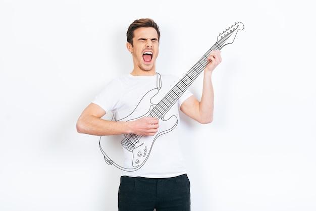 Как рок-звезда. молодой красавец играет на гитаре и держит рот открытым, стоя на белом фоне