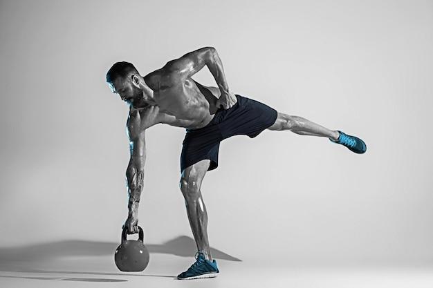 돌처럼. 네온 불빛에 스튜디오 배경 위에 젊은 백인 보디 빌딩 훈련. 무게가있는 근육질의 남성 모델. 스포츠, 보디 빌딩, 건강한 라이프 스타일, 동작 및 행동의 개념. 무료 사진