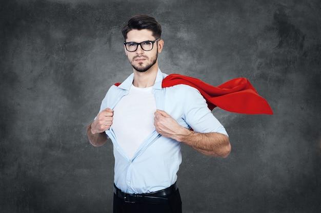 Как супергерой. уверенный молодой человек в плаще супергероя снимает рубашку и смотрит в камеру