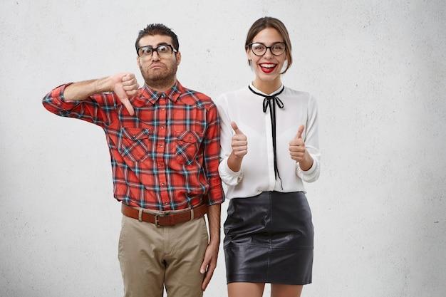 좋아하고 싫어하는 개념. 엄지 손가락으로 제스처를하는 여성 및 남성 동반자는 다른 감정을 표현합니다.