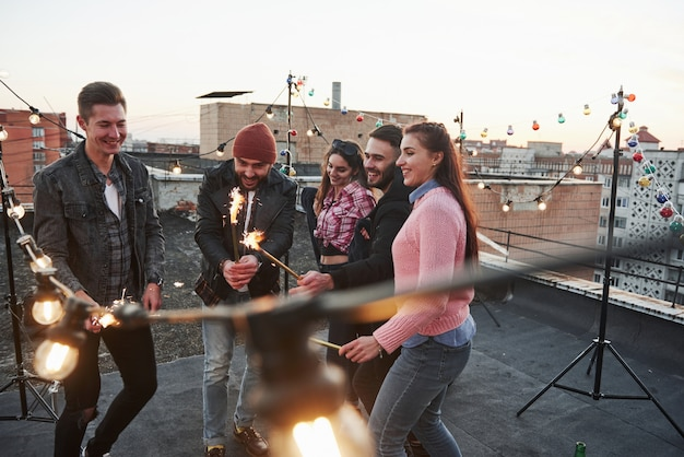 Like child again. playing with sparklers on the rooftop. group of young beautiful friends