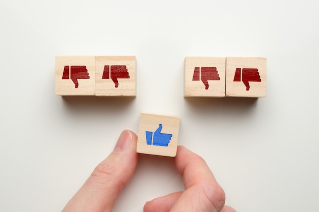 Like dislike concept on wooden cubes with hand.