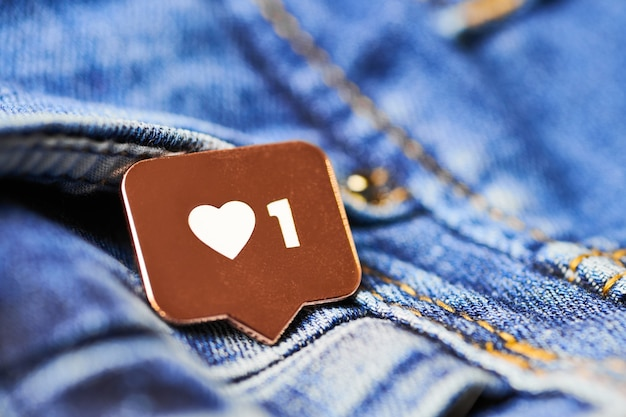 Как символ сердца. как кнопка знака, символ с сердцем и одной цифрой. маркетинг в социальных сетях. предпосылка текстуры синих джинсов.