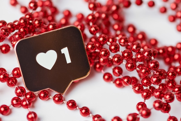 Как символ сердца. как кнопка знака, символ с сердцем и одной цифрой. маркетинг в социальных сетях. красный блеск бусины фон.