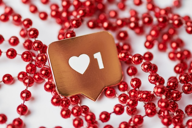 Like heart symbol. like sign button, symbol with heart and one digit. social media network marketing. red glitter beads background.