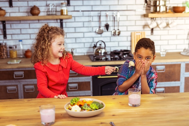 Do not like it. playful blonde girl expressing positivity while trying to feed her cousin