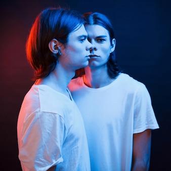 サイドミラーみたい。双子の兄弟の肖像画。ネオンの光で暗いスタジオで撮影したスタジオ