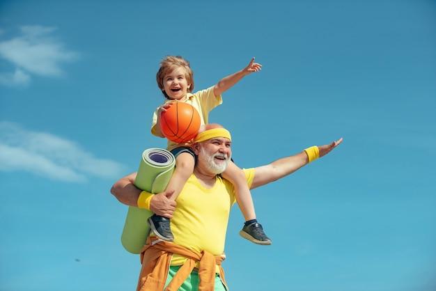 스포츠처럼 즐거운 노년의 남자와 하늘 위에서 스포츠와 건강한 생활 방식을 연습하는 귀여운 소년...