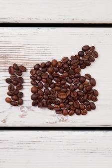 Like symbol made of coffee beans. thumb up on wihe wood.