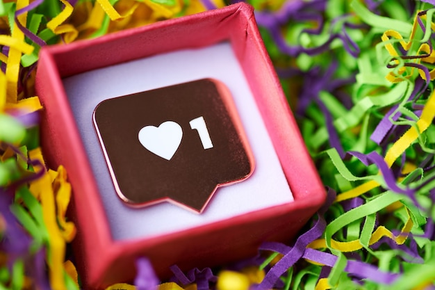 Like symbol in red gift box. like sign heart button, symbol with heart and one digit. social media network marketing. multicolored tinsel background.