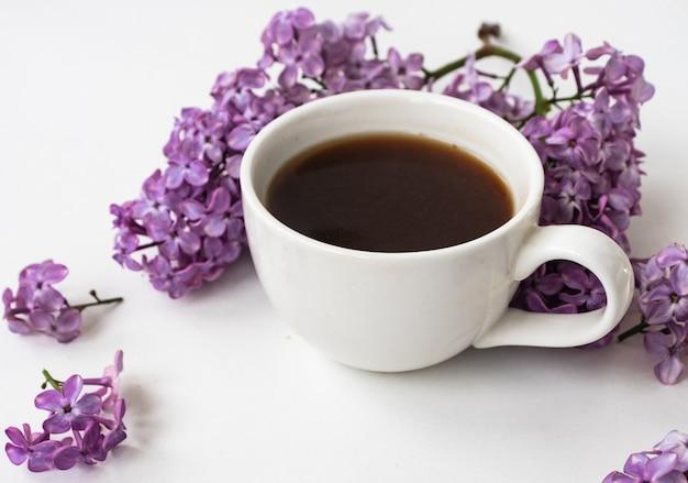 라일락과 흰색 나무 바탕에 평평한 스타일의 커피 한 잔. 아름다운 봄. 오버 헤드보기. 플랫 레이, 탑. 하계. 내츄럴한 봄 스타일.