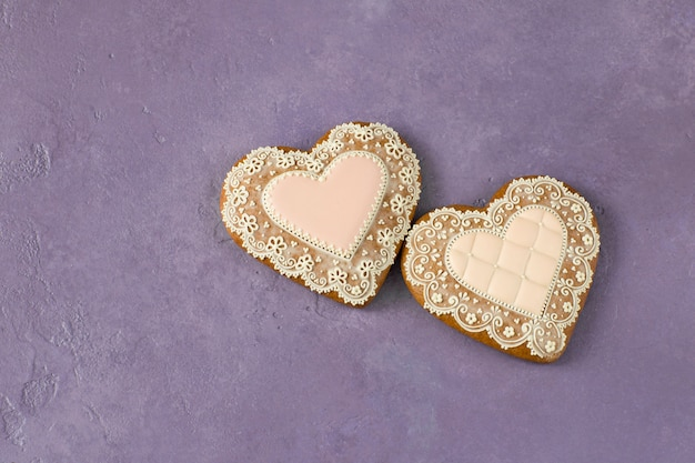 On a lilac background, two heart-shaped cakes and free space for text