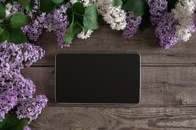 인사말 메시지 상단 보기를 위한 빈 공간이 있는 소박한 나무 배경 태블릿에 라일락 꽃