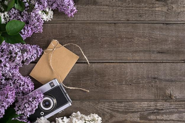 인사말 메시지 카메라 작은 봉투를 위한 빈 공간이 있는 소박한 나무 배경에 라일락 꽃...