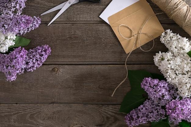 挨拶メッセージのための空のスペースで素朴な木製の背景にライラックの花。はさみ、糸巻き、小さな封筒。上面図。春の背景のコンセプトです。