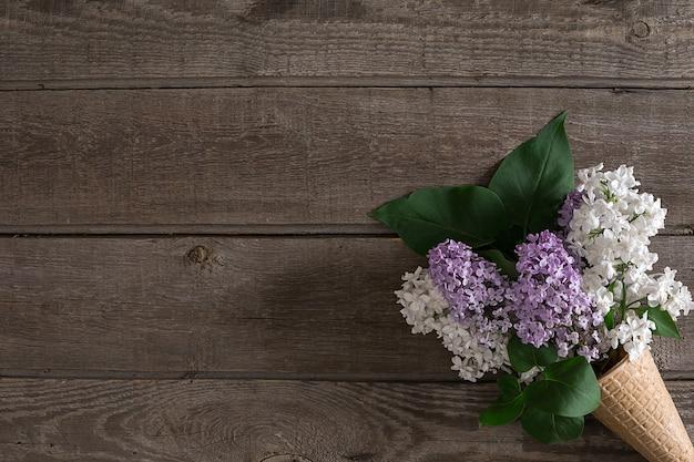 인사말 메시지 상단 보기를 위한 빈 공간이 있는 소박한 나무 배경에 라일락 꽃