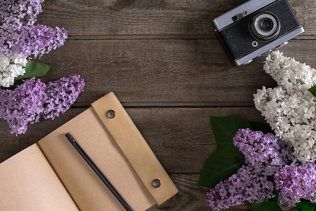 メッセージの挨拶のためのノートブックで素朴な木製の背景にライラックの花。上面図。春の背景のコンセプトです。