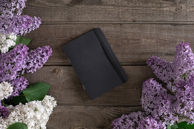 인사말 메시지 상단 보기를 위한 노트북이 있는 소박한 나무 배경에 라일락 꽃
