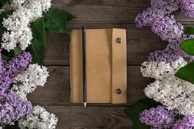 メッセージの挨拶のためのノートブックで素朴な木製の背景にライラックの花。