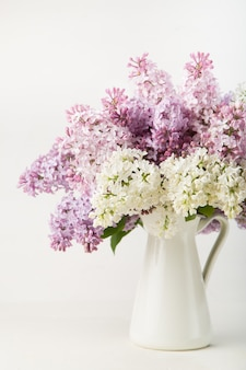 Lilac bouquet in a vase on white