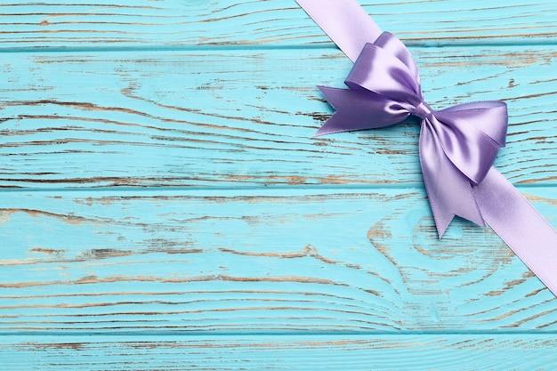 青い木製の背景にライラックの弓とリボン