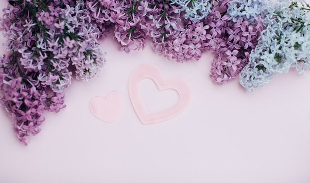 Lilac branches and two pink heart on a light pink background empty space for your text, top view.