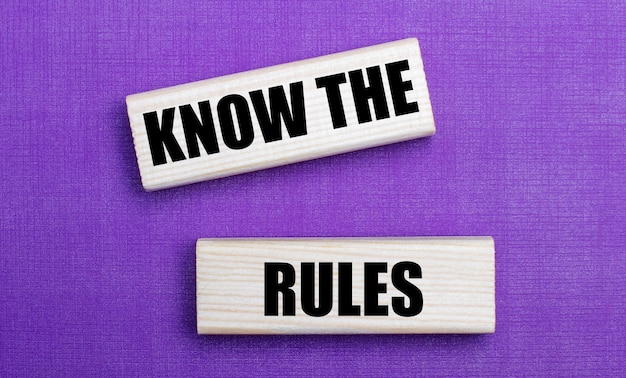 On a lilac bright background, light wooden blocks with the text know the rules