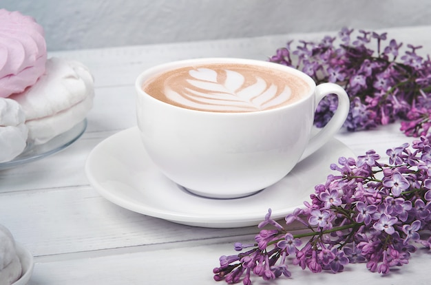 Lilac, coffee cup with latte art and marshmallow on white wooden table. flat lay