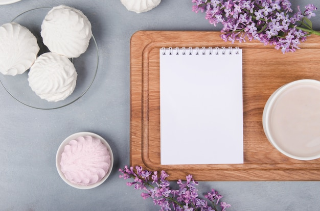 Lilac, coffee cup with latte art and marshmallow on white wooden table