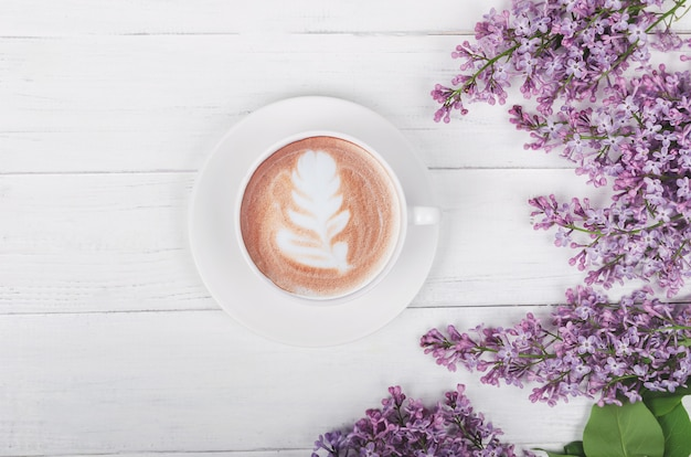 Lilac, coffee with latte art on light wooden table. romantic morning.flat lay