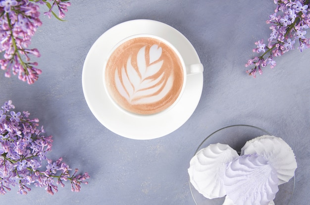 Lilac, coffee with latte art and marshmallow on gray wooden table. romantic morning. flat lay