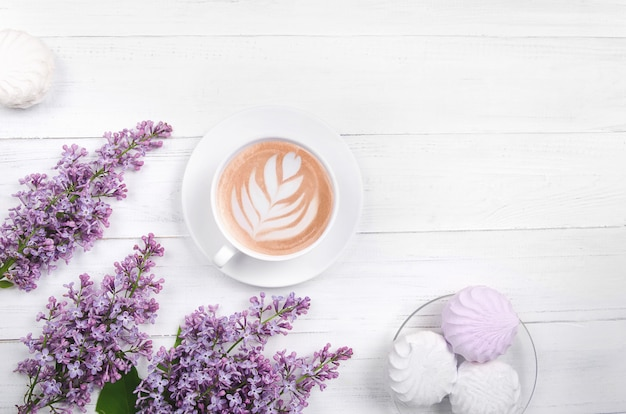 Lilac, coffee with latte art and marshmallow on white wooden table. romantic morning. flat lay