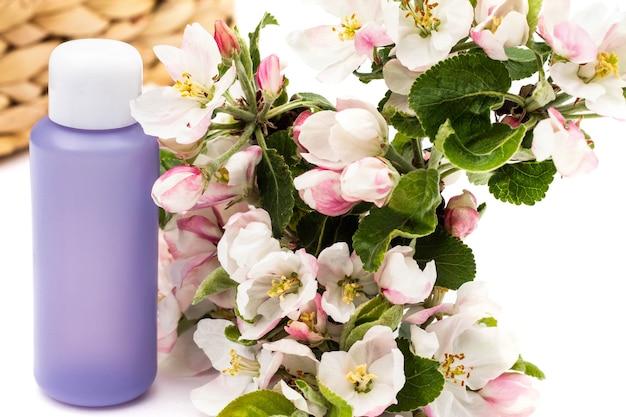 흰색 배경에 배 꽃이 있는 고리버들 바구니 근처에 라일락 화장품 병. 천연 유기농 화장품 개념입니다.